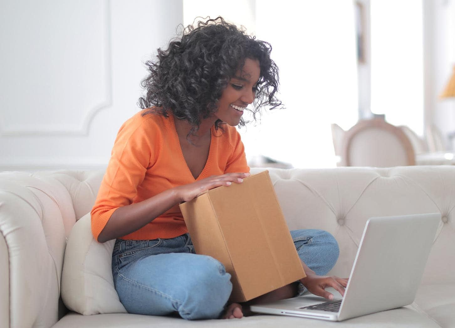 Black woman smiling with a cardboard box in her lap as she types on a laptop